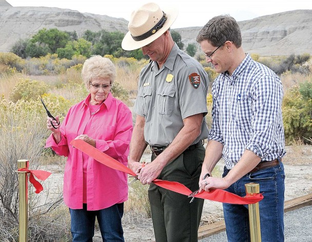 (David Peck photo) Karen Spragg, Mike Tranel and Cameron Miller cut the ribbon dedicating the Kane Historic Trail Friday morning at the town site east of Lovell. Dozens attended the open house and dedication.